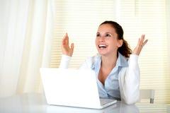 Mujer joven feliz que trabaja en la computadora portátil y que mira para arriba Foto de archivo libre de regalías