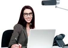 Mujer joven feliz que trabaja en oficina Imagenes de archivo