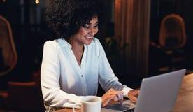 Mujer joven feliz que trabaja tarde en oficina imagenes de archivo