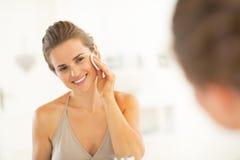 Mujer joven feliz que usa el cojín de algodón en cuarto de baño Imagen de archivo libre de regalías