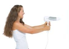 Mujer joven feliz que usa el hairdryer como arma Foto de archivo libre de regalías