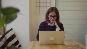Mujer joven feliz que usa el ordenador portátil en café almacen de video