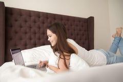 Mujer joven feliz que usa el ordenador portátil en dormitorio Imagen de archivo