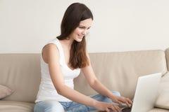 Mujer joven feliz que usa el ordenador portátil, trabajo de en línea casero Imagen de archivo