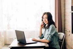 Mujer joven feliz que usa el ordenador port?til en casa imagen de archivo