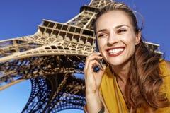 Mujer joven feliz que usa el teléfono celular contra la torre Eiffel, París fotos de archivo