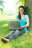 Mujer joven feliz que usa la computadora portátil al aire libre Imagenes de archivo