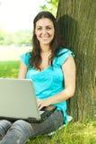 Mujer joven feliz que usa la computadora portátil al aire libre Fotografía de archivo libre de regalías