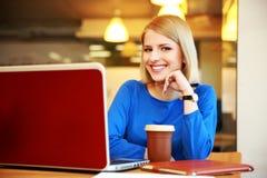 Mujer joven feliz que usa la computadora portátil Foto de archivo