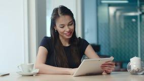 Mujer joven feliz que usa la tableta en una cafetería almacen de metraje de vídeo