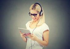 Mujer joven feliz que usa la tableta que escucha la música con los auriculares imagen de archivo libre de regalías
