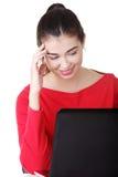 Mujer joven feliz que usa su computadora portátil. Foto de archivo