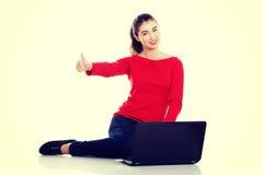 Mujer joven feliz que usa su ordenador portátil Imagenes de archivo