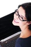 Mujer joven feliz que usa su ordenador portátil Imagen de archivo