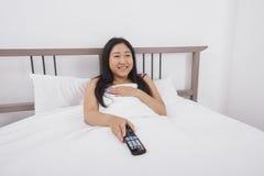 Mujer joven feliz que ve la TV en cama Fotos de archivo