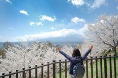 Mujer joven feliz que viaja con Cherry Blossom y el monte Fuji rosados hermosos en el área de templo roja de la pagoda de Chureit fotos de archivo