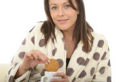 Mujer joven feliz relajada acogedora hermosa que goza de té y de las galletas Fotos de archivo