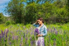 Mujer joven, feliz, situación entre el campo de los lupines violetas, sonriendo, flores púrpuras Cielo azul en el fondo Verano, c Imagen de archivo