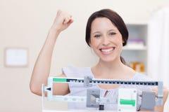 Mujer joven feliz sobre lo que muestra la escala Foto de archivo libre de regalías
