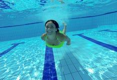 Mujer joven feliz sonriente bajo el agua en piscina Fotos de archivo libres de regalías