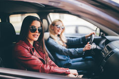 Mujer joven feliz sonriente que da a su amigo una elevación en su coche en ciudad, opinión del perfil a través de la ventana late Imagenes de archivo