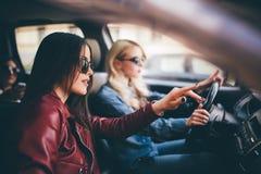 Mujer joven feliz sonriente que da a su amigo una elevación en su coche en ciudad, opinión del perfil a través de la ventana late Foto de archivo
