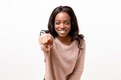 Mujer joven feliz sonriente que señala adelante Foto de archivo