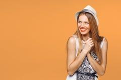 Mujer joven feliz sorprendida que mira de lado en el entusiasmo Aislado sobre fondo anaranjado fotografía de archivo