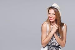Mujer joven feliz sorprendida que mira de lado en el entusiasmo Aislado sobre gris fotos de archivo libres de regalías
