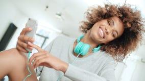 Mujer joven feliz y alegre que disfruta de música y que sostiene el teléfono Foto de archivo