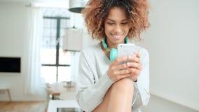 Mujer joven feliz y alegre que disfruta de música y que sostiene el teléfono Fotografía de archivo libre de regalías