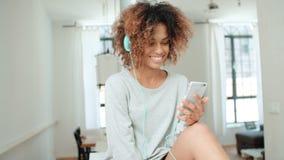 Mujer joven feliz y alegre que disfruta de música y que sostiene el teléfono Imagen de archivo