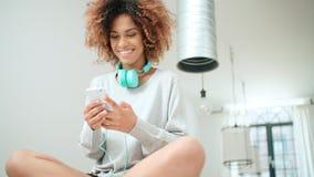 Mujer joven feliz y alegre que disfruta de música y que sostiene el teléfono Imágenes de archivo libres de regalías