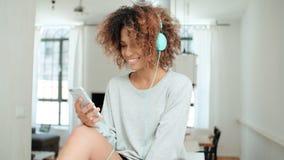 Mujer joven feliz y alegre que disfruta de música y que sostiene el teléfono Fotos de archivo