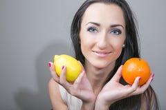 Mujer joven feliz y comida vegetariana sana, fruta Imagen de archivo libre de regalías