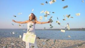 Mujer joven feliz y dinero que caen del cielo almacen de video