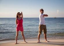 Mujer joven feliz y hombre que hacen ejercicios en la costa de mar Fotos de archivo