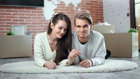 Mujer joven feliz y hombre que llevan a cabo las manos que sienten amor el plantear de la mentira en el piso que mira la cámara almacen de metraje de vídeo