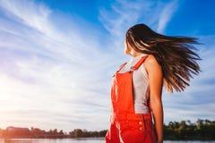 Mujer joven feliz y libre en fondo del cielo azul que disfruta de vida Foto de archivo