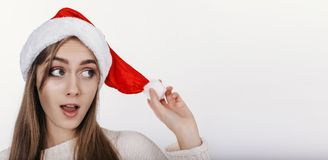 Mujer joven feliz y linda en el sombrero de santa que mira de lado Imágenes de archivo libres de regalías