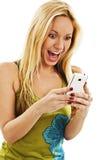 Mujer joven feliz y sorprendida que mira en el teléfono móvil Imagenes de archivo