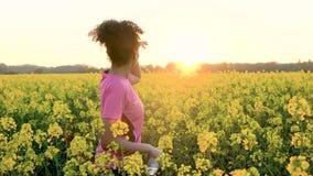 Mujer joven femenina del adolescente afroamericano de la muchacha que bebe de la botella de agua después de correr o de activar almacen de metraje de vídeo
