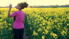 Mujer joven femenina del adolescente afroamericano de la muchacha que bebe de la botella de agua y que corre o que activa metrajes