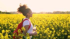 Mujer joven femenina del adolescente afroamericano de la muchacha que camina con la mochila y la botella de agua rojas en el camp metrajes