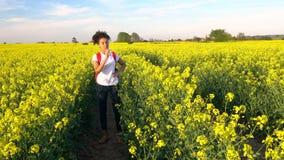 Mujer joven femenina del adolescente afroamericano de la muchacha que camina con la mochila y la botella rojas de agua en campo d metrajes