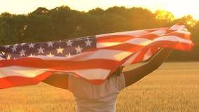 Mujer joven femenina del adolescente afroamericano de la muchacha que sostiene una bandera americana de las barras y estrellas de almacen de video