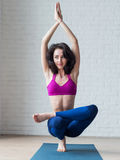 Mujer joven flaca linda que hace la postura Padangustasana de la balanza del soporte del dedo del pie durante la sesión de la yog foto de archivo