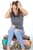 Mujer joven frustrada enojada que se sienta en una maleta que tira de su pelo Fotos de archivo