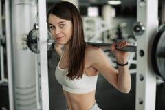 Mujer joven fuerte con el cuerpo atl?tico hermoso que hace ejercicios con el barbell Aptitud, levantamiento de pesas Cuidado m?di imagenes de archivo
