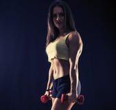 Mujer joven fuerte con pesas de gimnasia fotografía de archivo libre de regalías